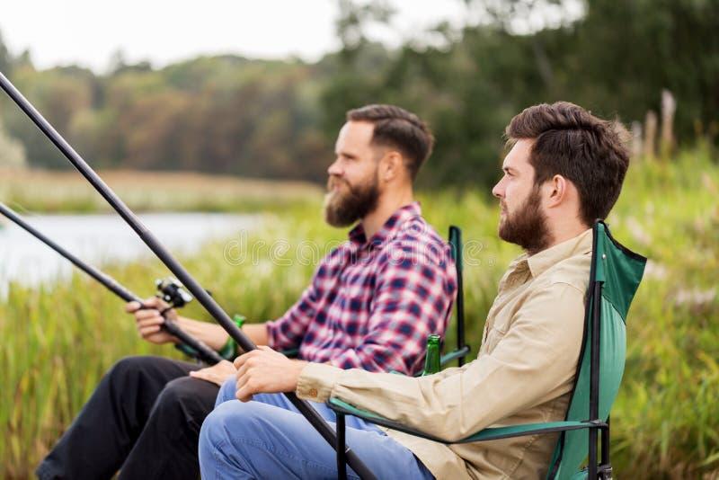 Manliga vänner med metspön på sjön arkivfoton