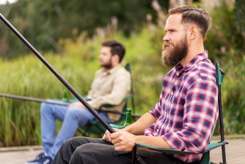 Manliga vänner med metspön på sjön arkivfoto