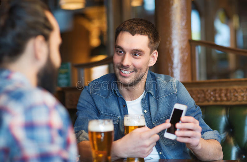 Manliga vänner med smartphonen som dricker öl på stången