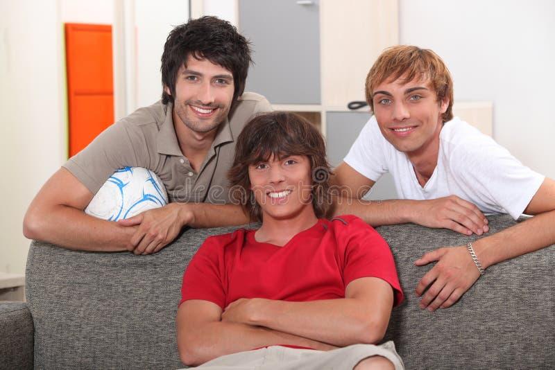 Manliga vänner på en soffa. arkivfoto