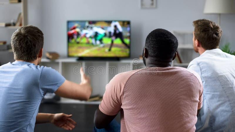 Manliga vänner samlar för att hålla ögonen på fotbollkonkurrens på den stora skärmen, soffaexperter royaltyfria foton