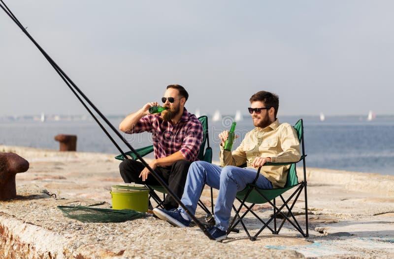 Manliga vänner som fiskar och dricker öl på pir royaltyfri bild