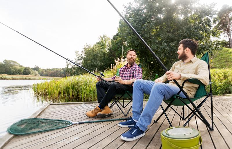 Manliga vänner som fiskar och dricker öl på sjön royaltyfri fotografi