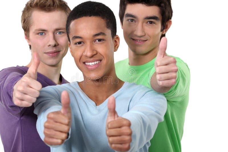 Manliga vänner som ger tummar-upp royaltyfri bild