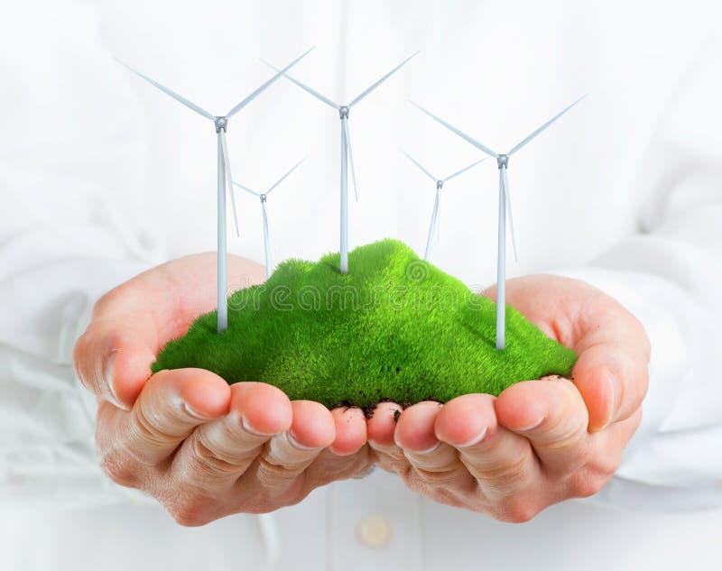 Manlign räcker innehav som en grön kull med lindar turbiner arkivbild
