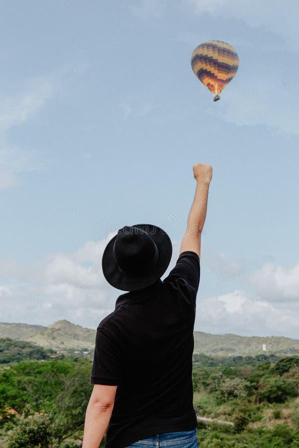 Manligt anseende med hans arm och näve som lyfts in i luften och en ballong för varm luft som flyger bakgrunden royaltyfri foto