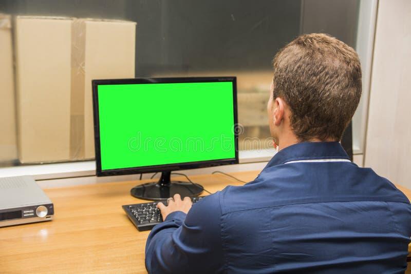 Manligt arbetarsammanträde för ungt kontor på hans skrivbord royaltyfria foton