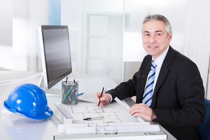 Manligt arbete för mogen arkitekt på skrivbordet arkivfoton