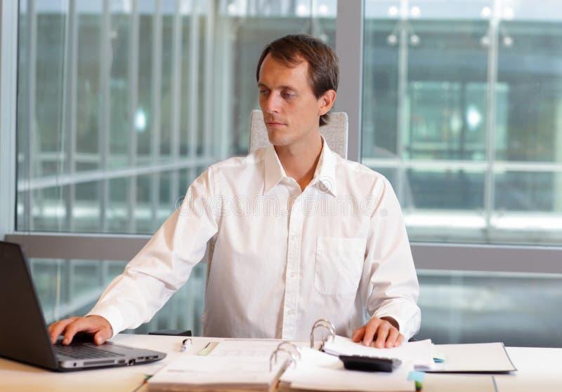 Manligt arbete med bärbara datorn i hans kontor arkivbilder