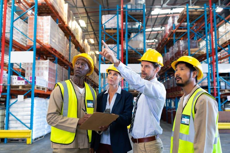Manligt arbetsledareanseende med coworkers och peka på avståndet i lager royaltyfria foton