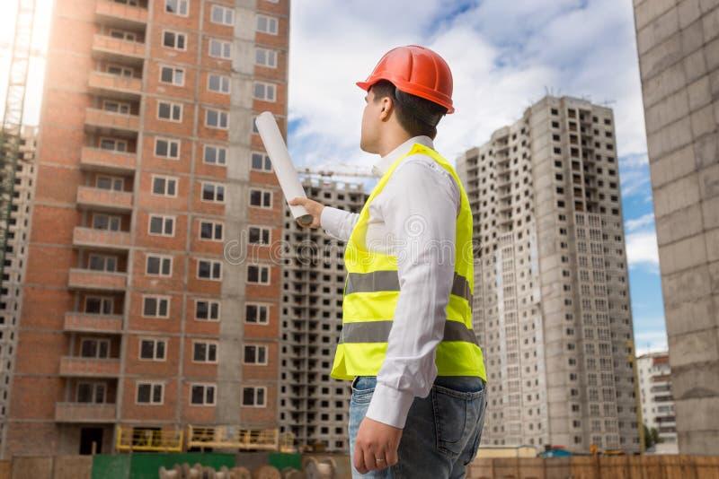 Manligt arkitektanseende på byggnadsplats och peka på byggnader under konstruktion med ritningar arkivfoton