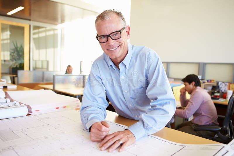 Manligt arkitektStudying Plans In kontor arkivfoto