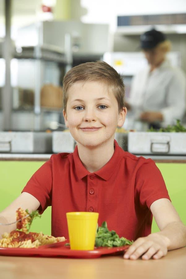 Manligt elevsammanträde på tabellen i skolakafeterian som äter sunt L arkivbilder