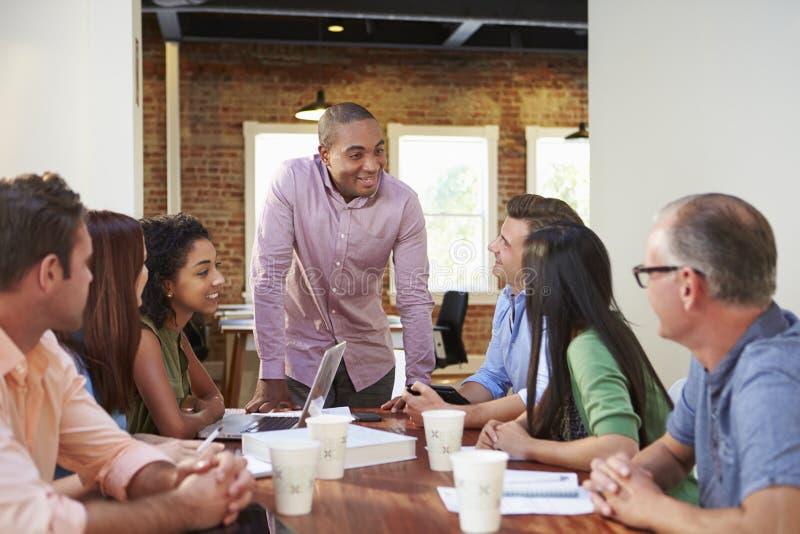 Manligt framstickande Addressing Office Workers på mötet royaltyfri fotografi