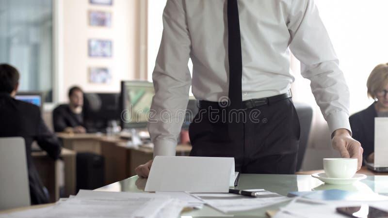 Manligt framstickande som ser till och med dokumentation och dricker te som st?r i hans kontor arkivbild