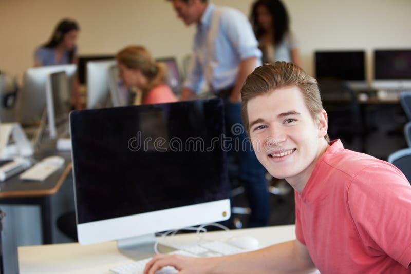 Manligt högskolestudentUsing Computer In klassrum arkivfoton