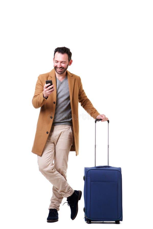 Manligt handelsresandeanseende för full längd med mobiltelefonen och resväskan mot vit bakgrund arkivbild