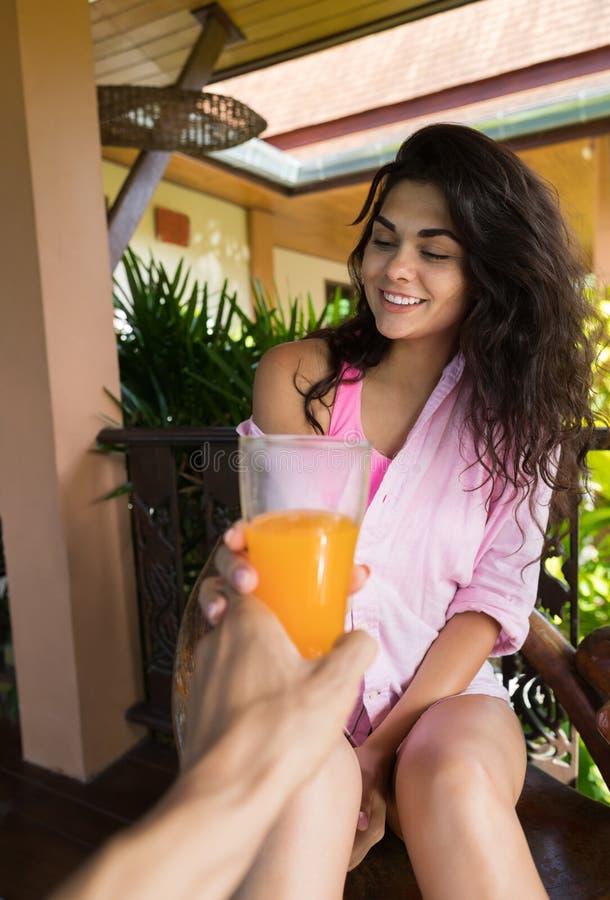 Manligt handhållexponeringsglas med orange Juice Giving To Smiling Woman, lyckligt par i morgon arkivfoton