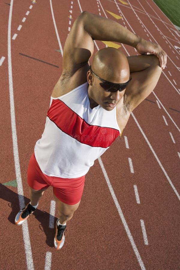 Manligt idrottsman nenStretching On Race spår fotografering för bildbyråer