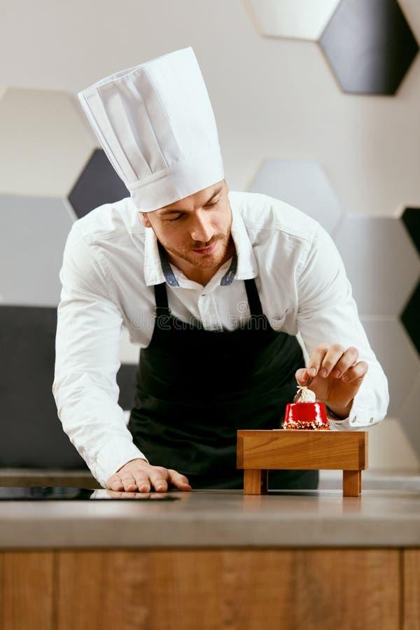 Manligt konditorDecorating Dessert In kök arkivbilder