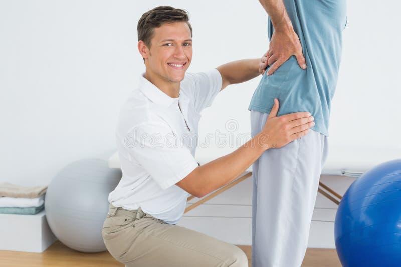 Manligt massera för terapeut mans lägre baksida på idrottshallsjukhuset arkivbild