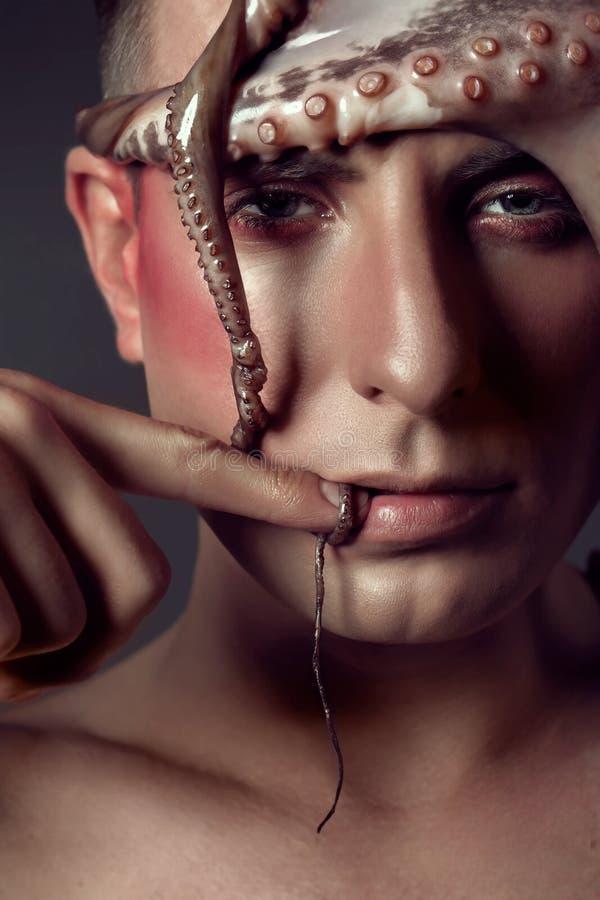 Manligt modellslut upp ståenden med sminket och bläckfisken, begrepp för havsliv royaltyfri fotografi