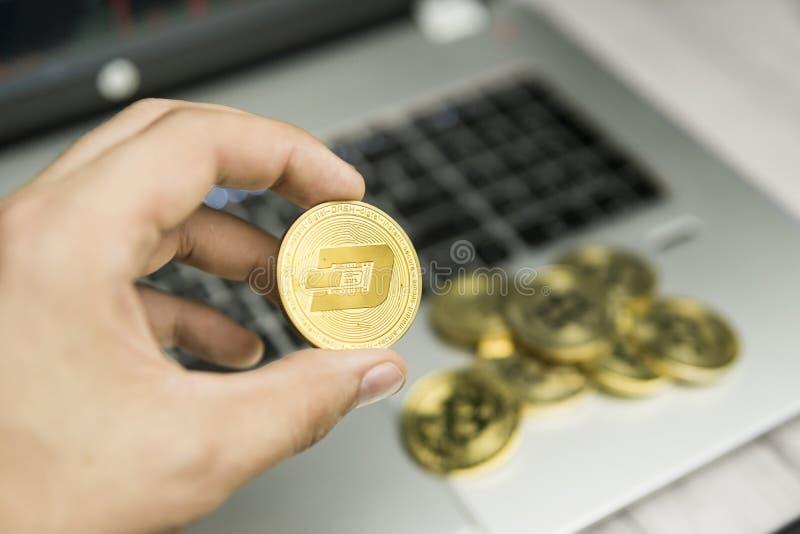 Manligt mynt för streck för affärsmanhandinnehav på en bakgrund av bärbar datortangentbordet och högen av guld- mynt Faktiska pen royaltyfri foto