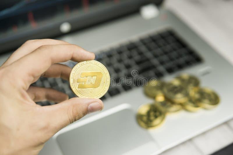 Manligt mynt för streck för affärsmanhandinnehav på en bakgrund av bärbar datortangentbordet och högen av guld- mynt Faktiska pen arkivbilder