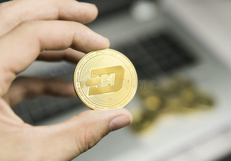 Manligt mynt för streck för affärsmanhandinnehav på en bakgrund av bärbar datortangentbordet och högen av guld- mynt Faktiska pen royaltyfri fotografi