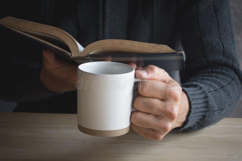 Manligt papper för kopp för svart kaffe som läser en bok royaltyfria bilder