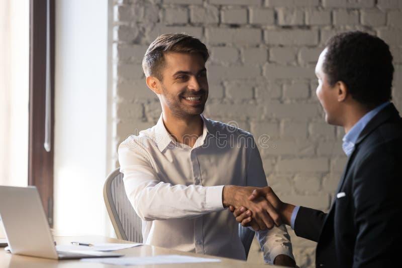 Manligt sökande för upphetsad affärsmanhandskakning på jobbintervjun royaltyfri foto
