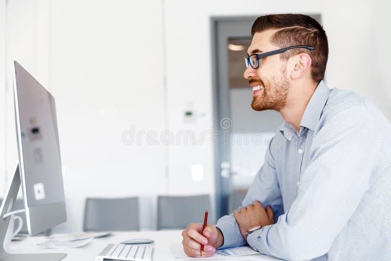 Manligt sammanträde för kontorsarbetare på skrivbordet fotografering för bildbyråer