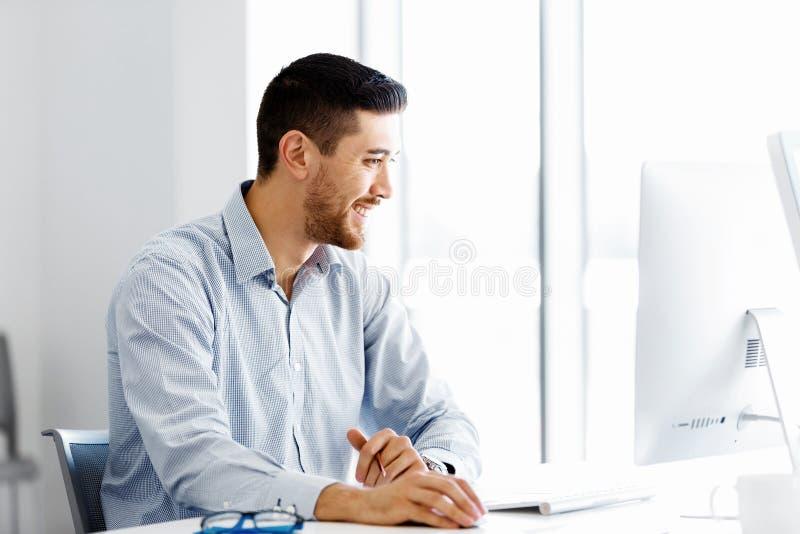 Manligt sammanträde för kontorsarbetare på skrivbordet arkivfoton