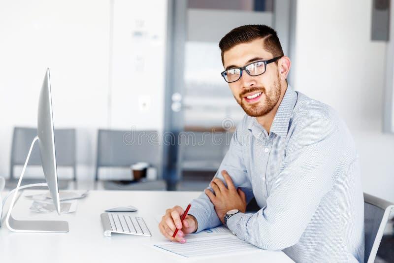 Manligt sammanträde för kontorsarbetare på skrivbordet arkivbild