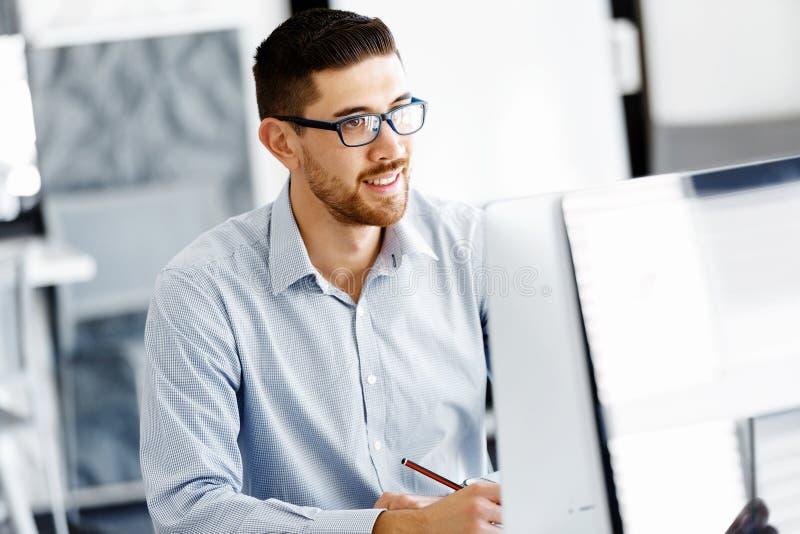 Manligt sammanträde för kontorsarbetare på skrivbordet royaltyfri fotografi