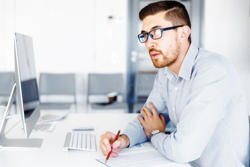 Manligt sammanträde för kontorsarbetare på skrivbordet royaltyfria foton