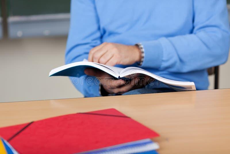 Manligt sammanträde för professor Holding Book While på skrivbordet royaltyfria bilder