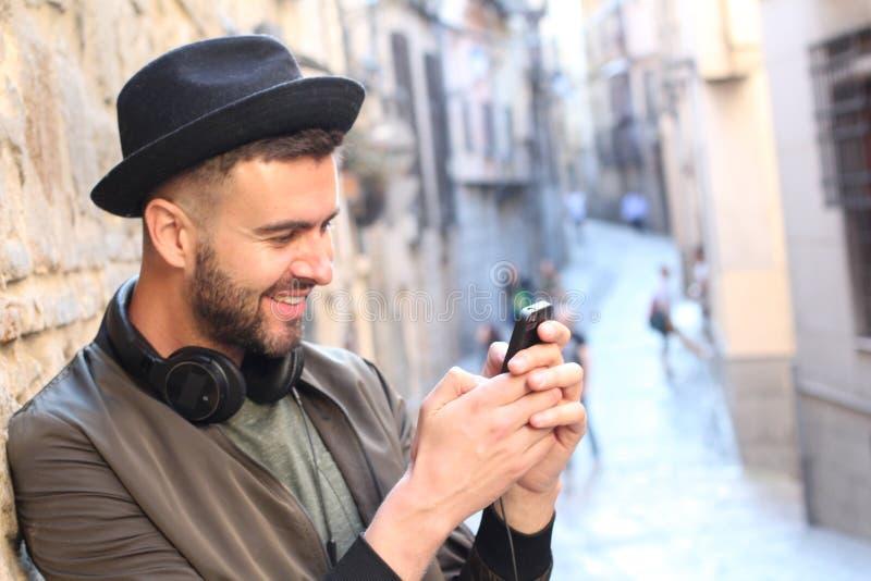 Manligt skratta, medan smsa utomhus royaltyfri bild