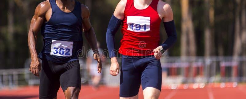 Manligt sprinta för idrottsman nen Två män i sportkläder som körs på det rinnande spåret i yrkesmässig stadion arkivbild