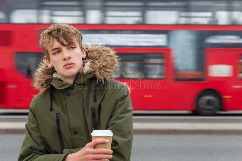 Manligt ungt vuxet tonårigt dricka kaffe med den röda London bussen royaltyfria bilder