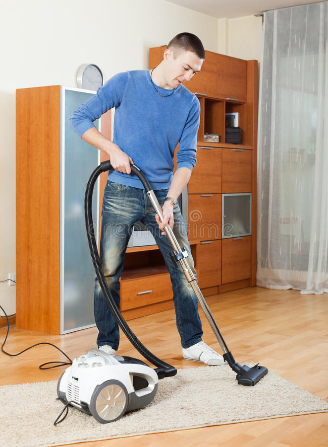Manlokalvård med dammsugare i vardagsrum fotografering för bildbyråer