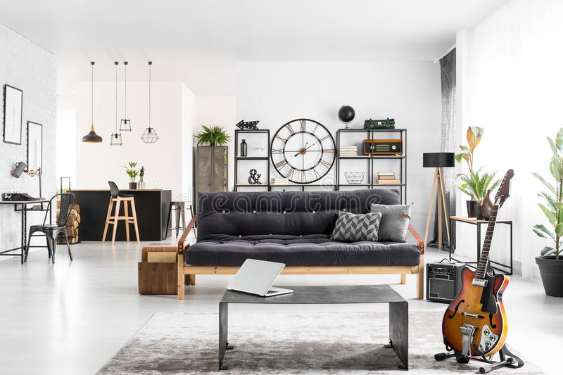 Manly apartment interior. With black couch, laptop on an industrial table and electric guitar stock photography