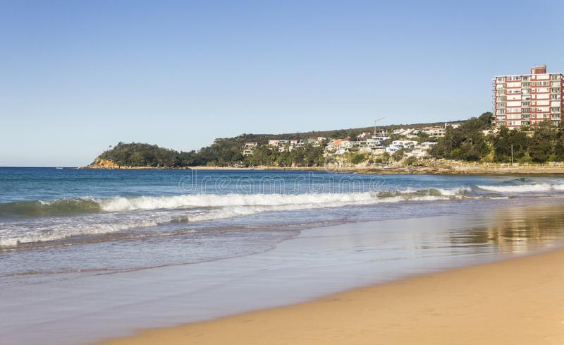 Manly Beach, Australia. The clear blue waves meet the orange sand of Manly Beach in Sydney, Australia, with a condo in the background, from 2019 stock images