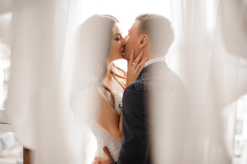 Manly groom and beautiful bride kissing against white background stock photo