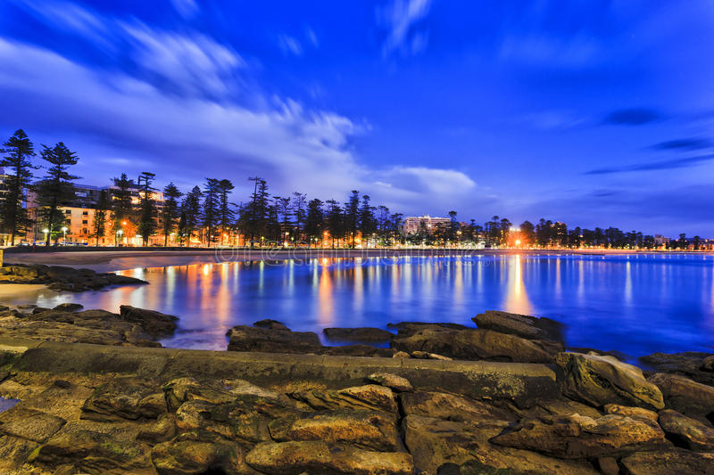 Manly Waterfront Blue Rise. Manly beach waterfront facing Pacific ocean along line of trees and local businesses and houses at blue hour at dawn with rocky stock photos