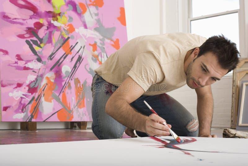 Manmålning på kanfas i studio arkivbild