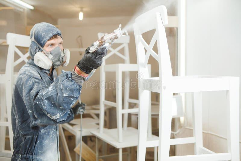 Manmålningstol in i vit målarfärg i respiratorisk maskering Applikation av flamman - retardant se till brandskydd royaltyfri foto