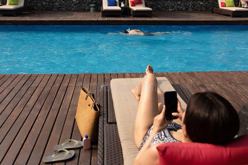 Mannübungsschwimmen im Pool mit der unscharfen Frau, die Handy im Vordergrund verwendet lizenzfreie stockfotografie