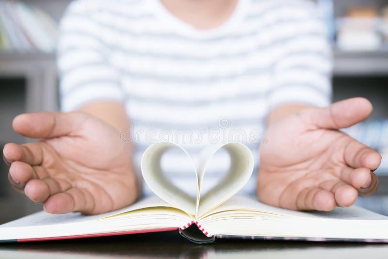 Mann öffnen das Handshowbuch mit offenen Seiten falten ein Blatt Papier Herz auf hölzerner Tabelle stockfotografie