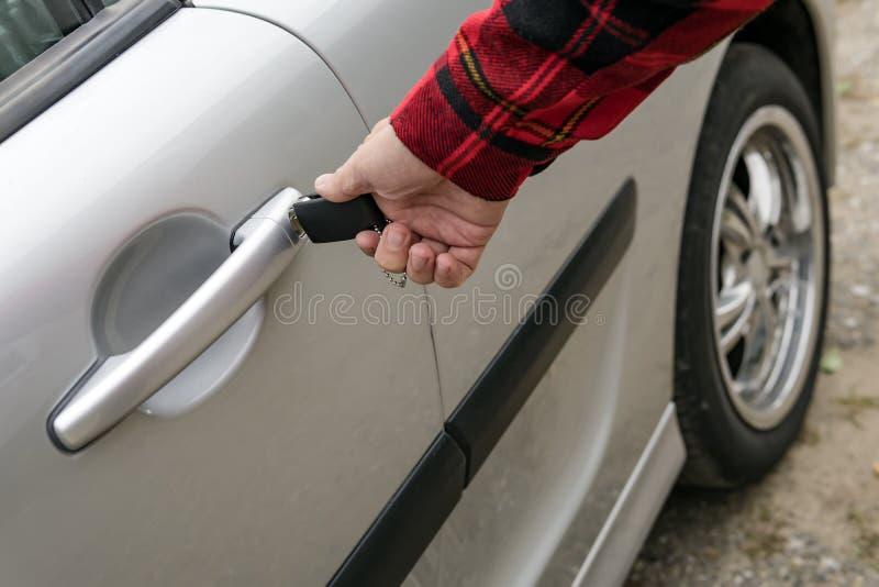 Mann öffnet mechanisch seine Einfügetaste des Autos Drehen des Schlüssels im Schlüsselloch auf dem Türgriff eines Parkfahrzeugs R lizenzfreie stockbilder